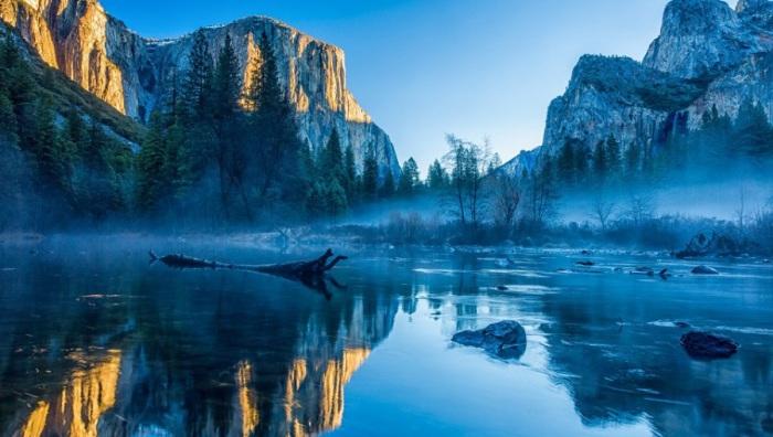 Горная речка медленно катит свои воды сквозь горных великанов, отражающихся в ее спокойной поверхности.